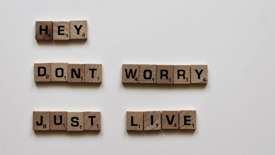 """Testo """"Hey, don't worry just live"""" su cubetti di legno e sfondo bianco seguendo lo stile delle lettere del gioco """"Scarabeo""""."""