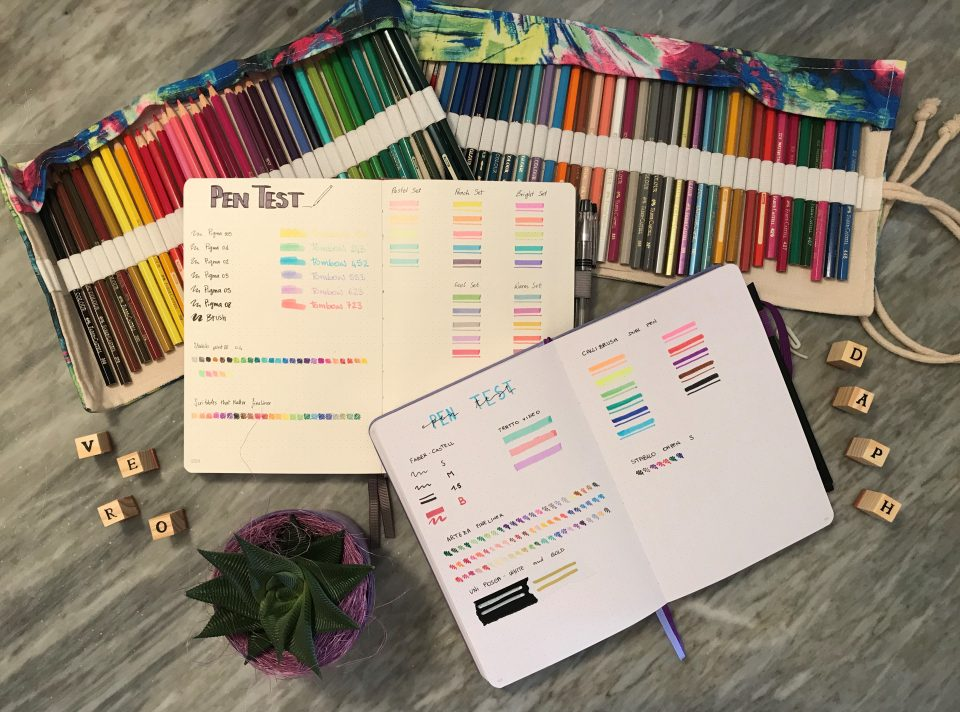 Immagine esempio del pen test di due bullet journal con i pastelli sullo sfondo.