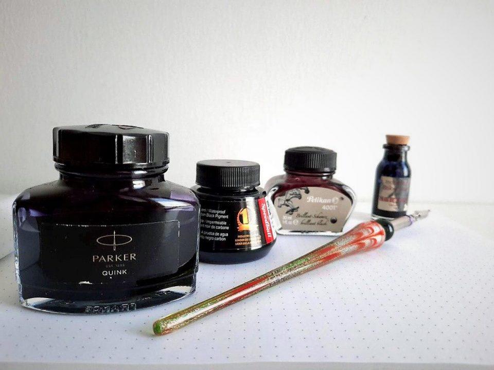 foto di quattro inchiostri di diverse marche e una penna per pennini in vetro colorato su un quaderno